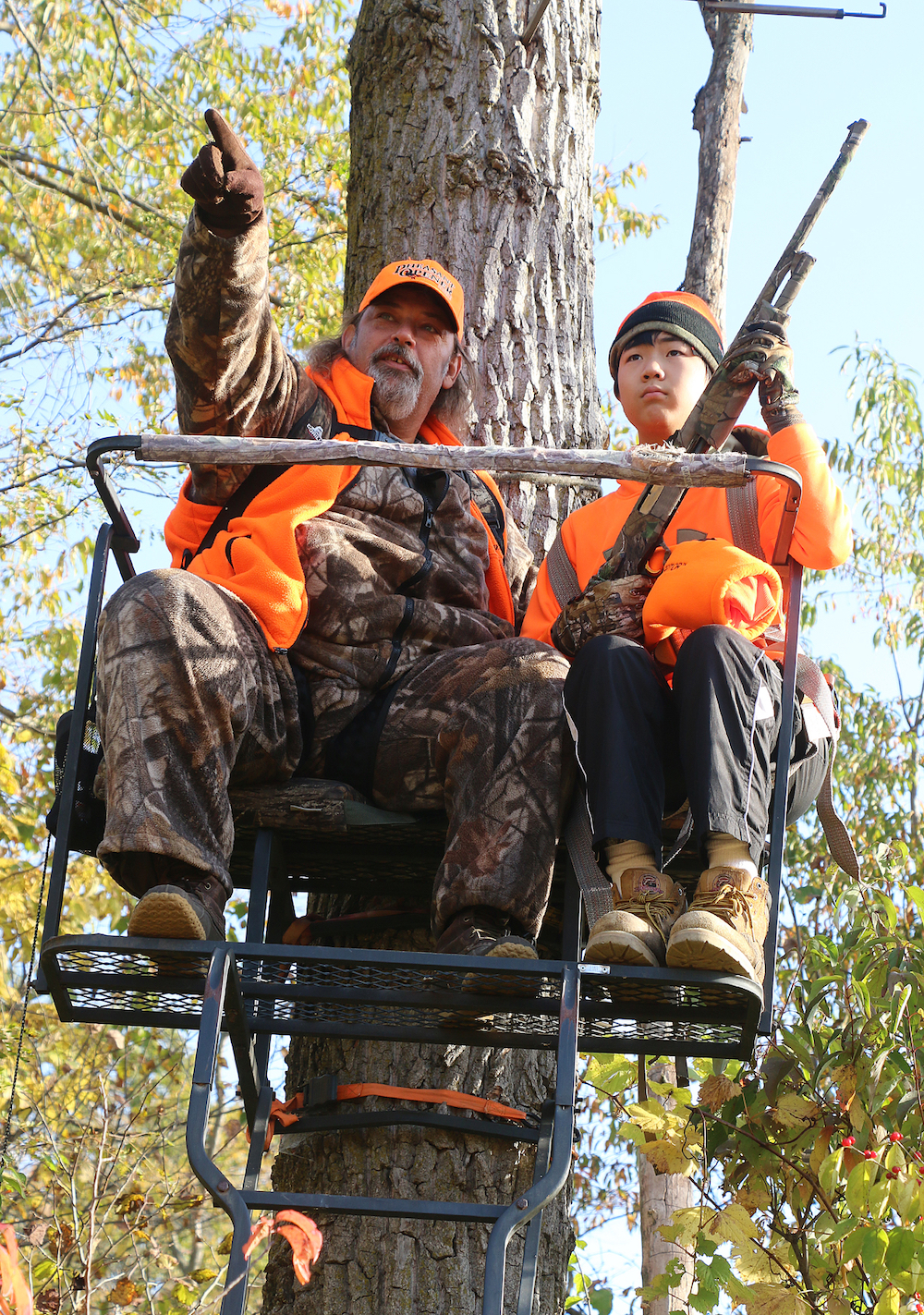 Two deer hunters wearing blaze orange hats and jackets are sitting in a tree-stand.