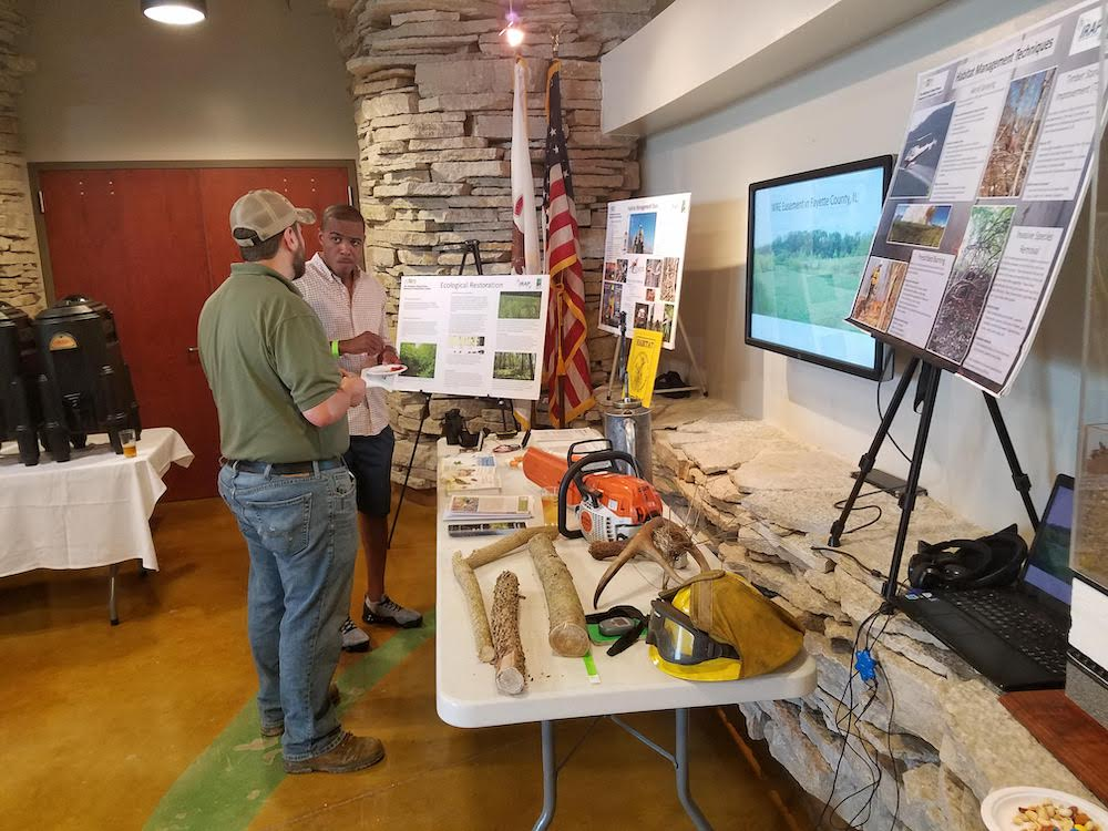 Two people converse in front of an informational poster and a table with various object relating to habitat restoration and conservation.