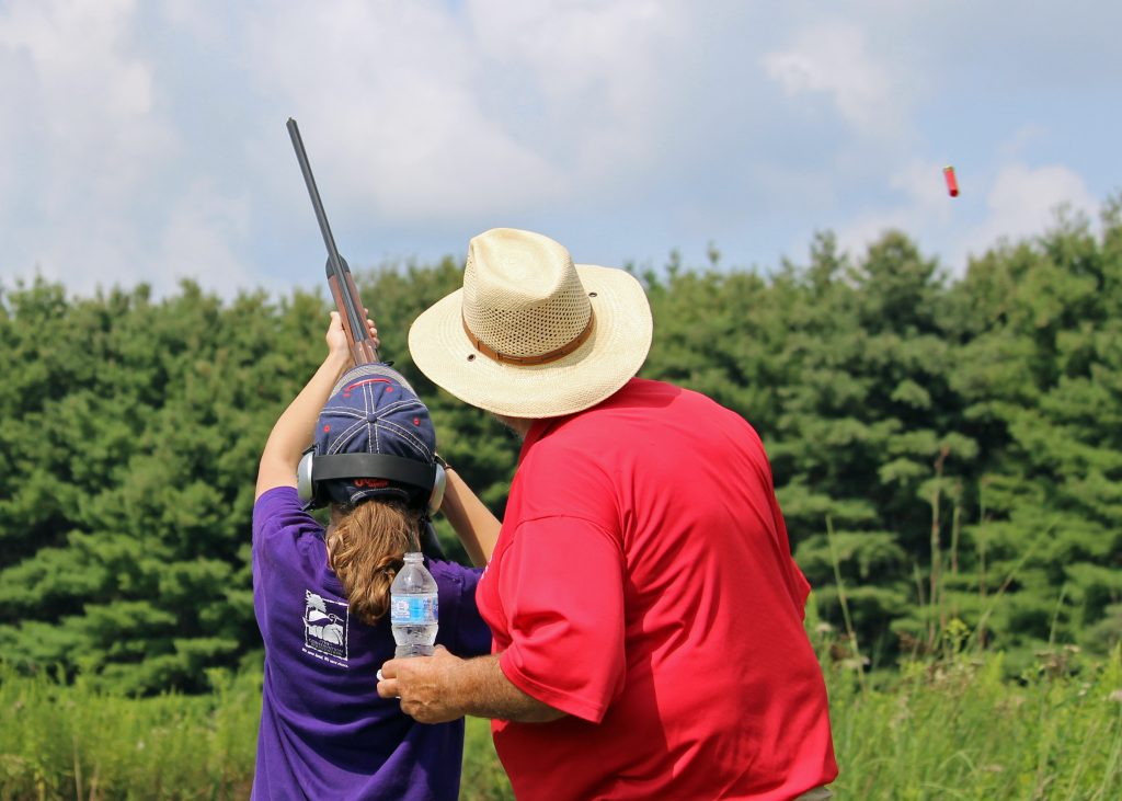 An adult in a wide brimmed hat and red shirt guides a youth hunter in a purple shirt and navy ball cap in shooting practice. Tall green pine trees are in the background.