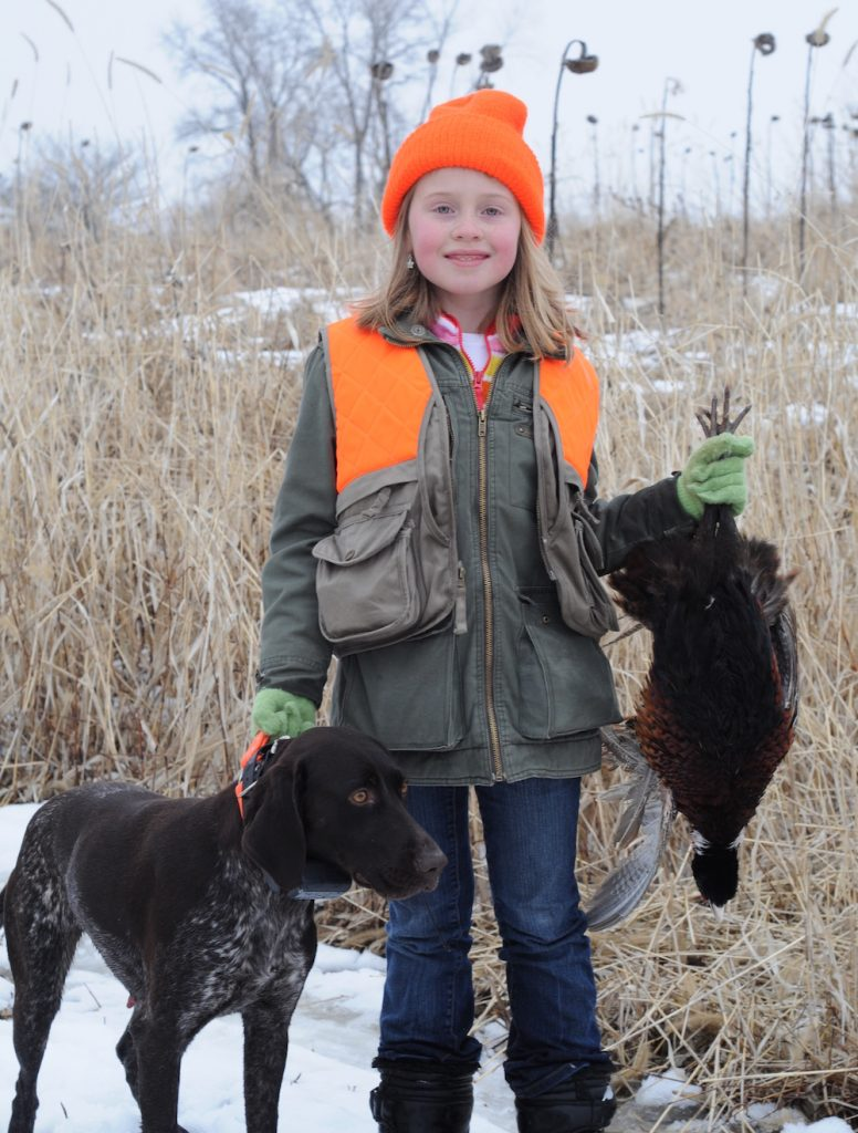 A successful youth hunter in a blaze orange stocking cap and vest holds up a harvested pheasant in her left hand and holds the collar of her hunting dog in her right.