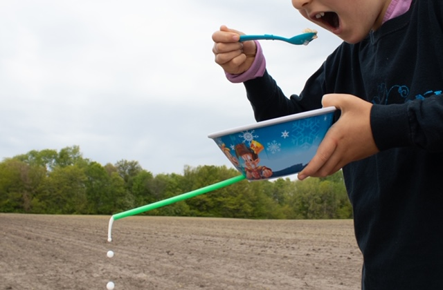 A young child eats cereal out of a bowl. The bowl has a hole drilled in it with a straw poked through at the bottom. Milk is dripping out of the straw. An agricultural field is in the background.