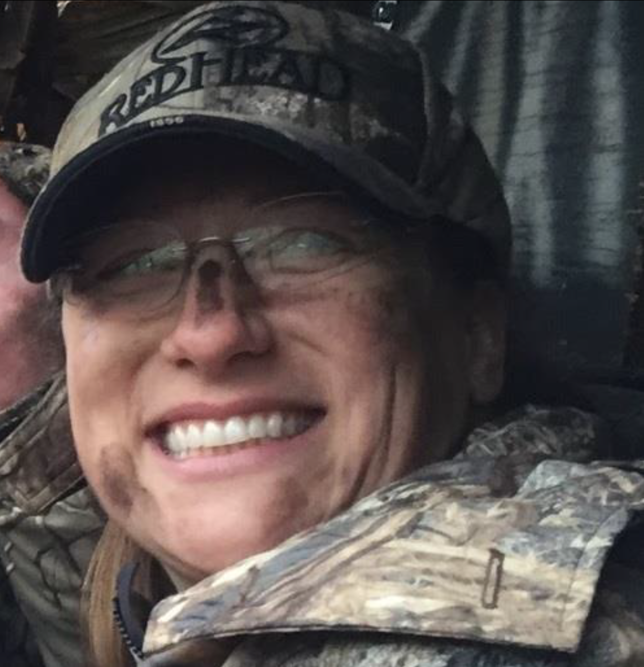 A close-up portrait of a smiling young woman wearing camouflage gear and a camouflage hat.