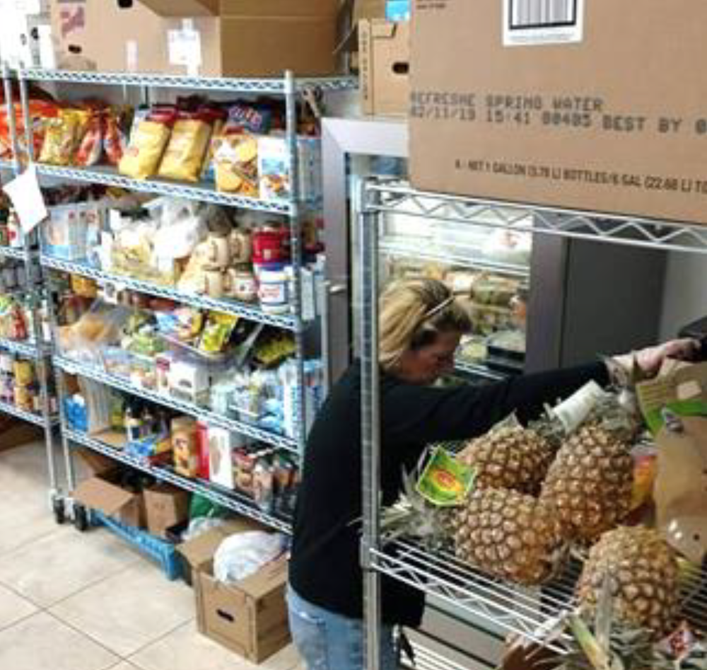 A woman sorting and putting away food at a food bank. Shelves of food are behind and in front of her.