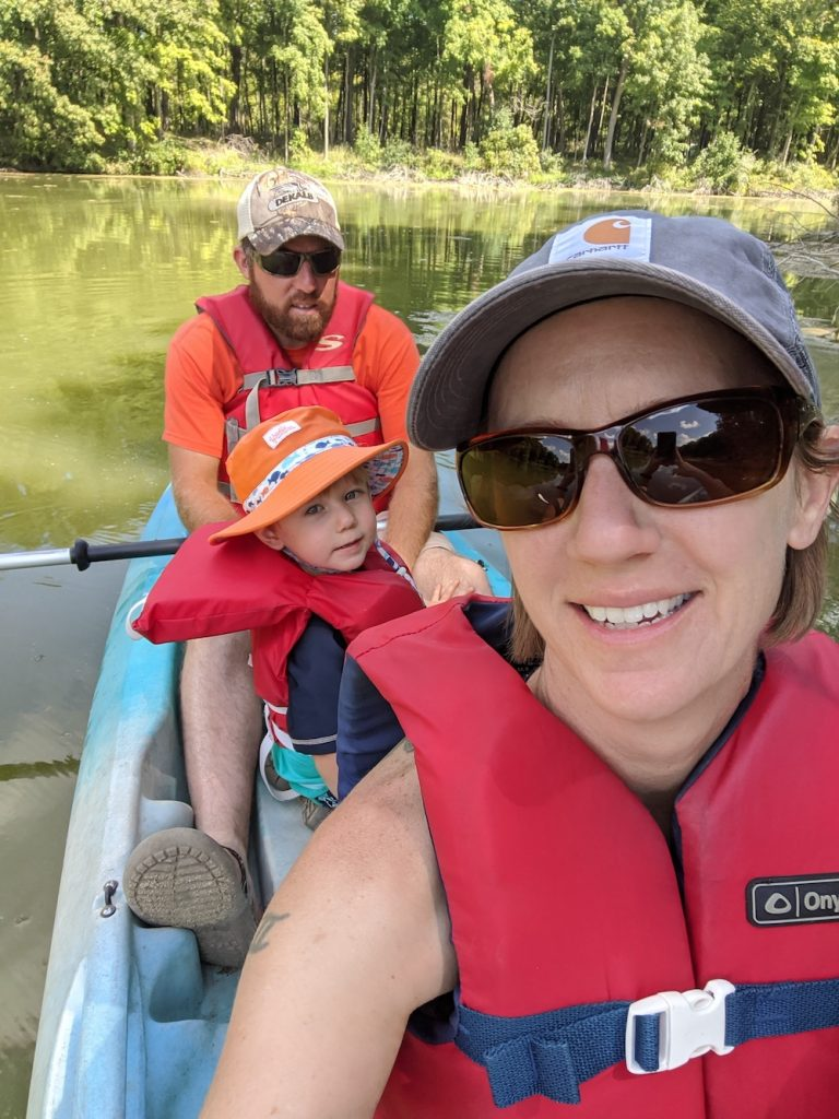 A family comprised of a man, woman, and child all wearing red floatation vests are enjoying a canoe ride on a river.