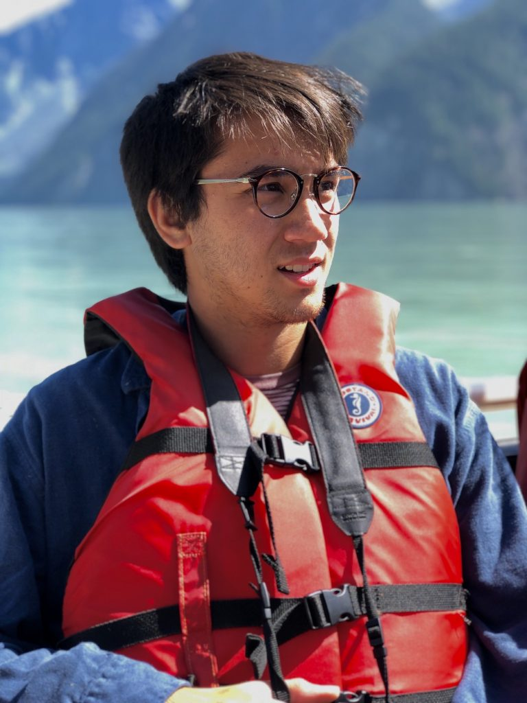A man on a boat wears a red life jacket with a blue long sleeve shirt underneath. He gazes off to the right. In the background is the water of a lake or bay and mountains.