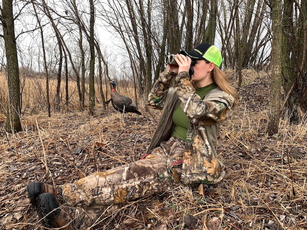 A hunter in camouflage is sitting on the ground at the edge of a forest and looks through hand-held binoculars. In the background is a wild turkey decoy.