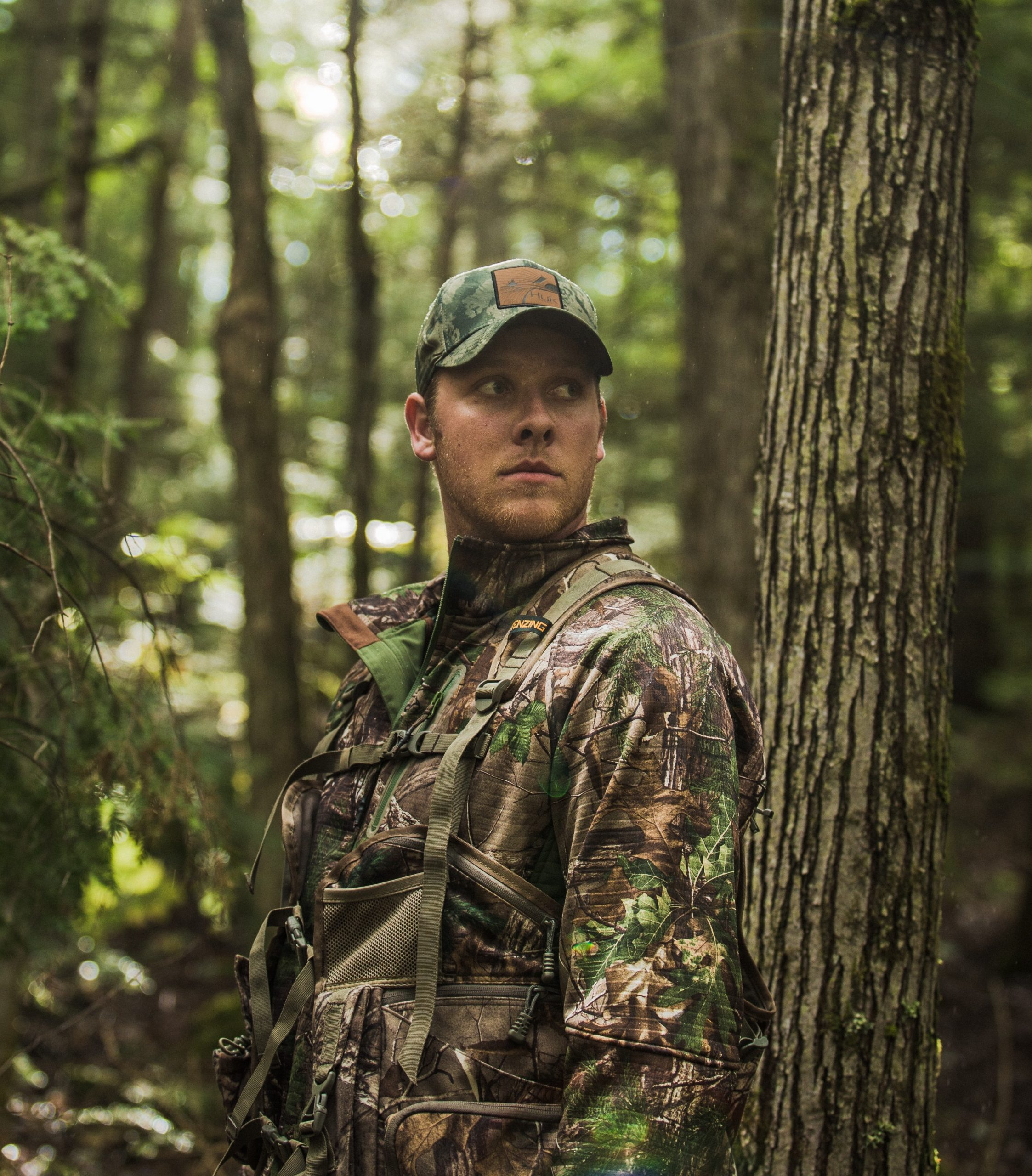 In a lush green forest a hunter in camouflage gear looks to the right.