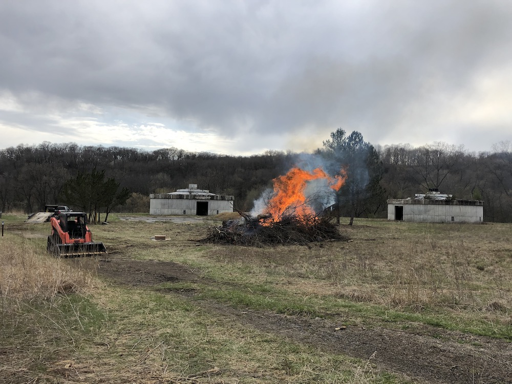 A pile of brush and tree limbs is on fire. Behind the fire are concrete structures. In the background is a woodland. In the foreground is a grassy area and a small tractor.