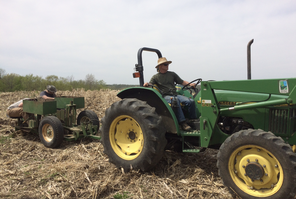 A man wearing a wide brimmed hat drives a tractor and pulls a tree planting implements with two men working on it. The tractor is moving across an agricultural field.