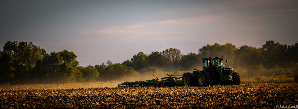 A farmer drives a green tractor pulling a tillage implement in an agricultural field. In the background are trees and a blue sky.