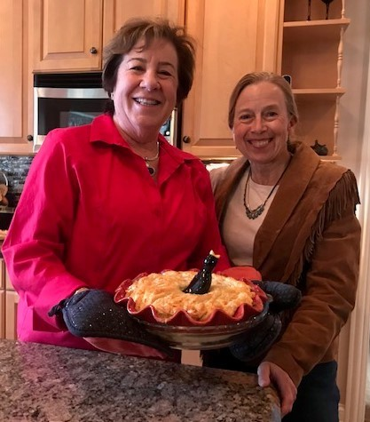 Two women pose behind a pie in a  kitchen.