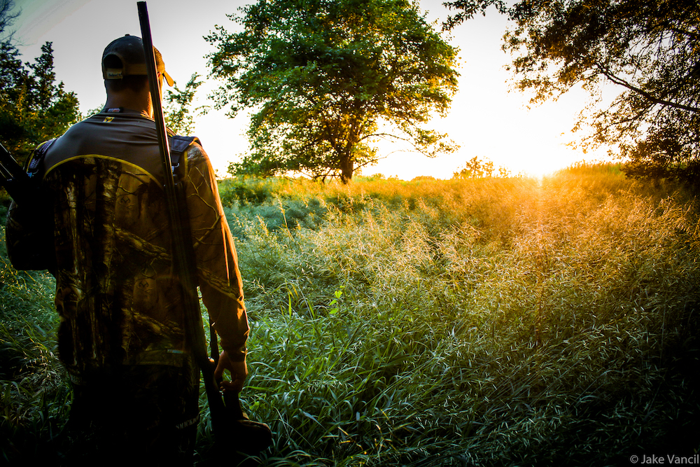 A hunter walks towards a grassy area. A tree and sunrise are in the distance.
