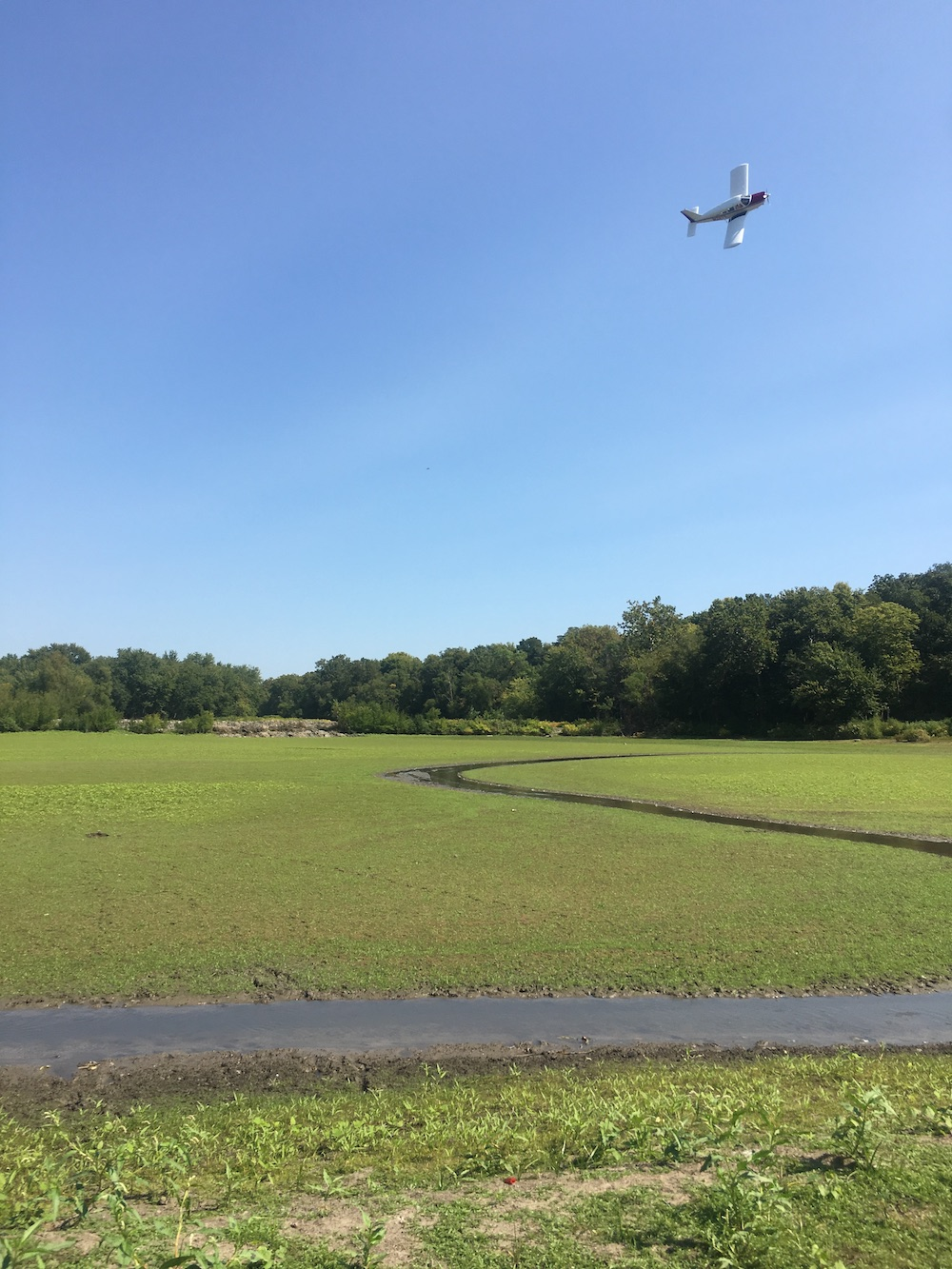 A small airplane flies low and on its side over a lush green waterway. Trees are in the background with a blue sky above.