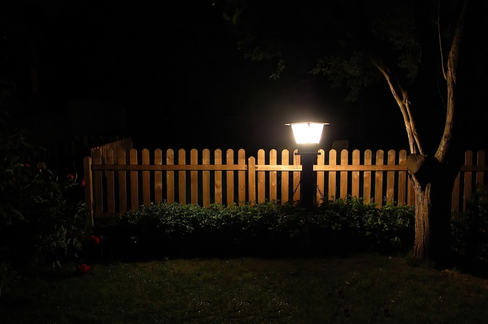 A nighttime backyard with a light on  along a fence with bushes.