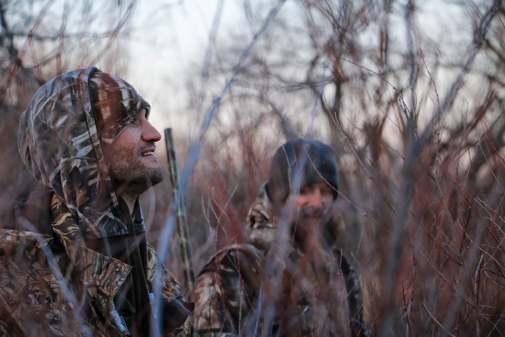 In winter two men in camouflage gear and a shotgun enjoy the morning. They are surrounded by vegetation. Trees are in the background.
