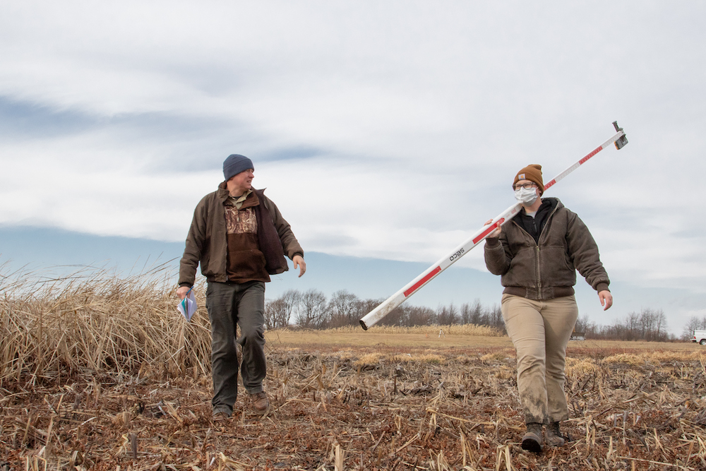 Two researchers with surveying equipment walk through an agricultural field during winter. A cloudy sky is in the background.