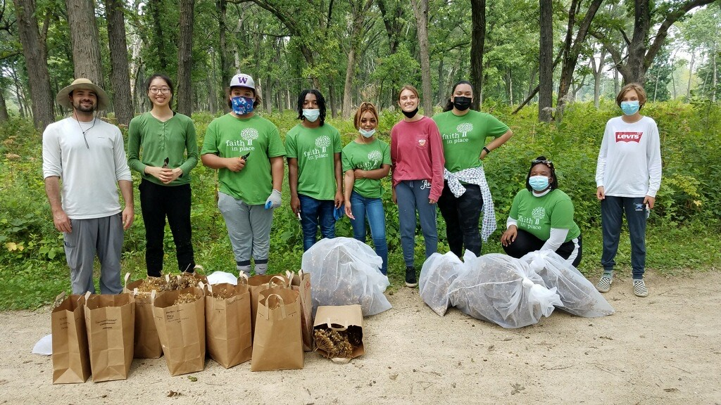 A group of young people stand behind bags of collected prairie seed. In the background is a lush green forest.