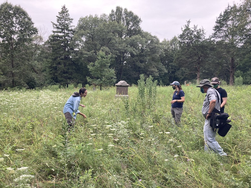 A group of people taking a hike through a prairie near an old cemetery. Trees are in the background against a gray sky.